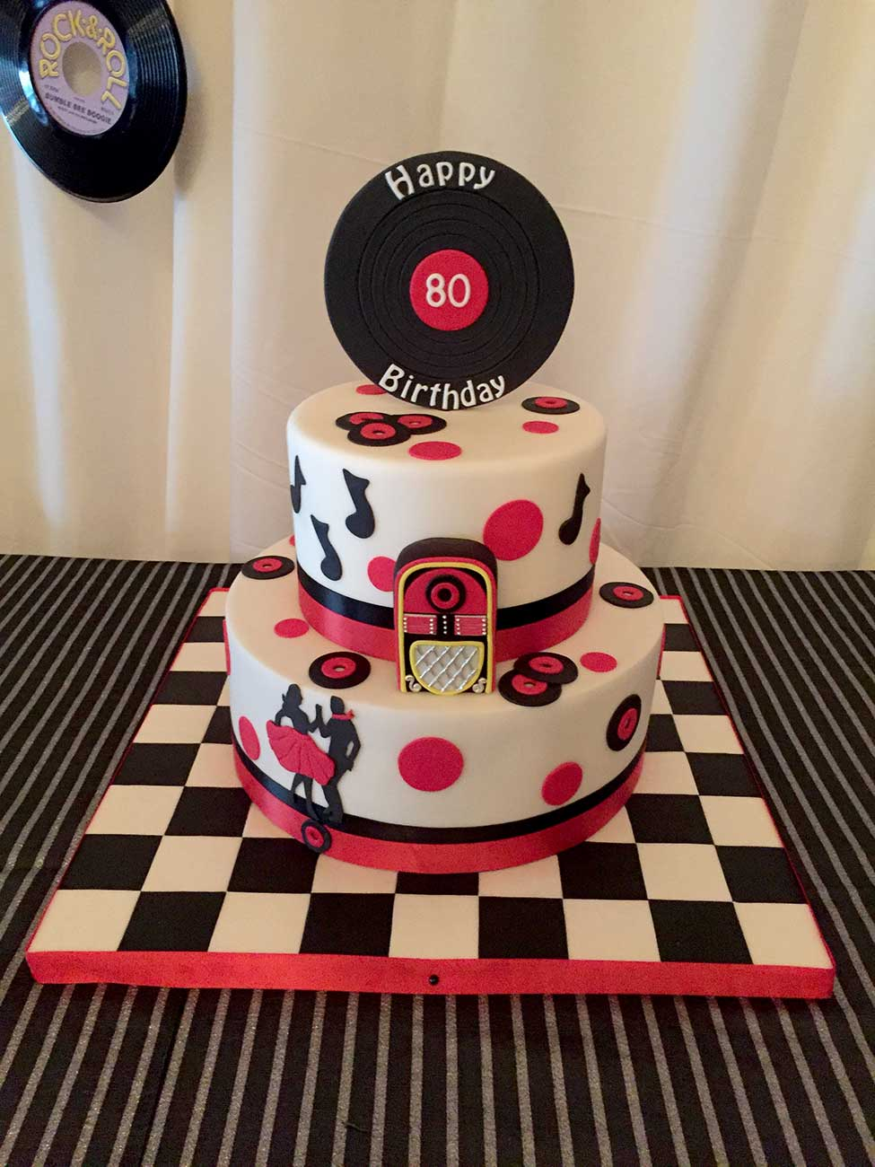 2 tiered wedding cake with a small record on top that says Happy 80 Birthday