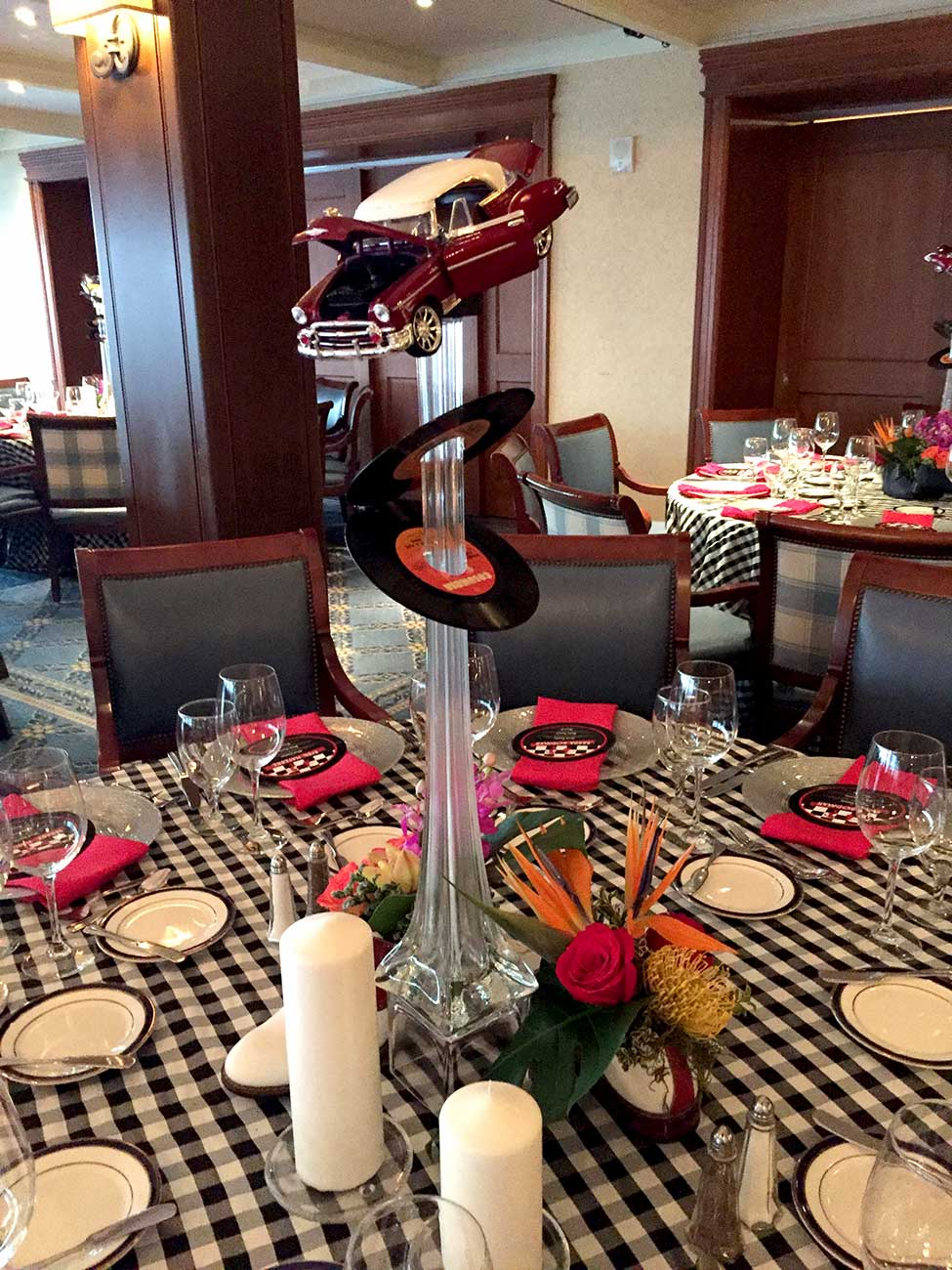 Tabletop decor in a 50's theme with dinnerware, crystal and a 50's car and record floral centerpiece