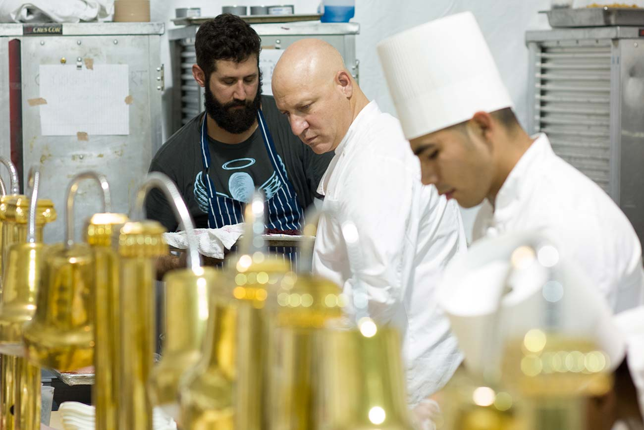 Chef Tom Colicchio cooking in a kitchen with 2 assistants