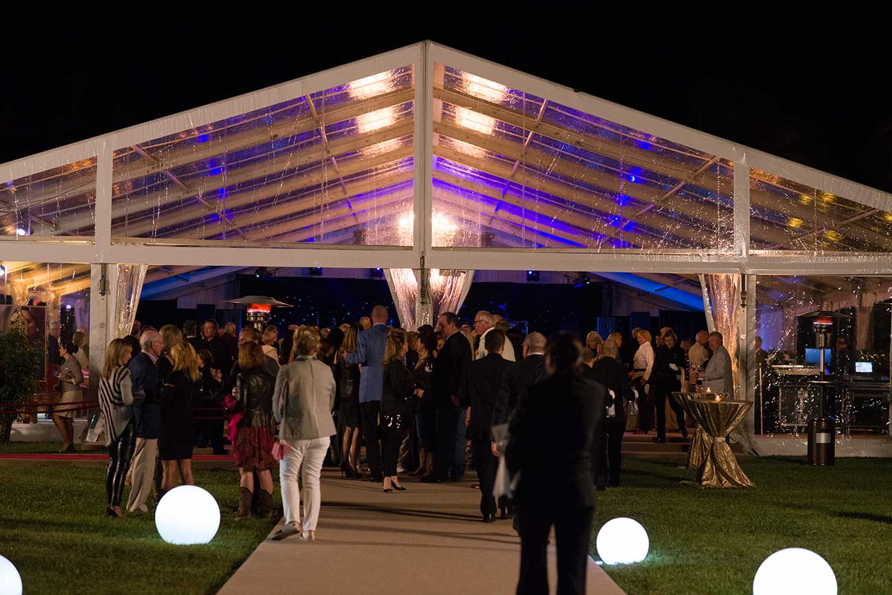 People outside an outdoor event tent at night