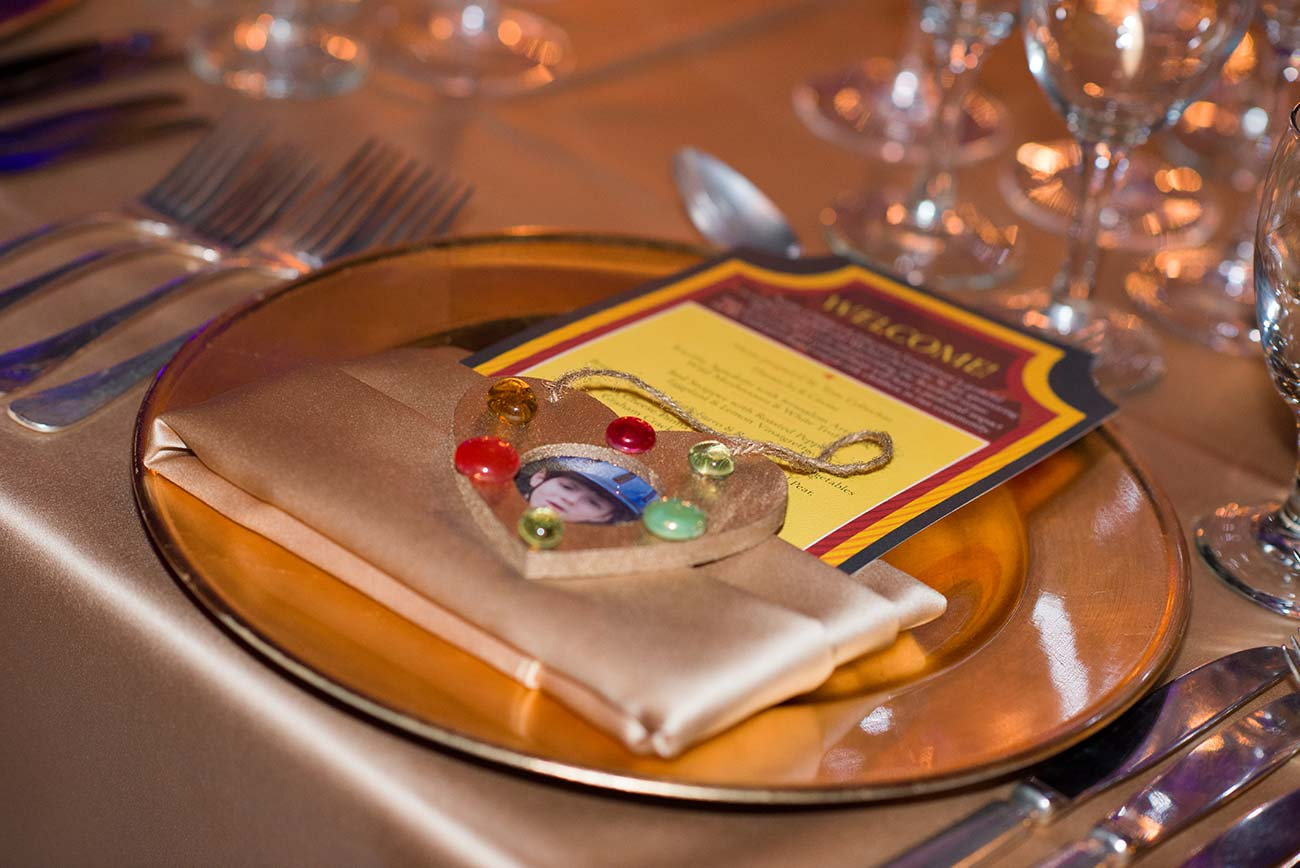 Designed event brochure tucked inside a champagne colored napkin over a charger