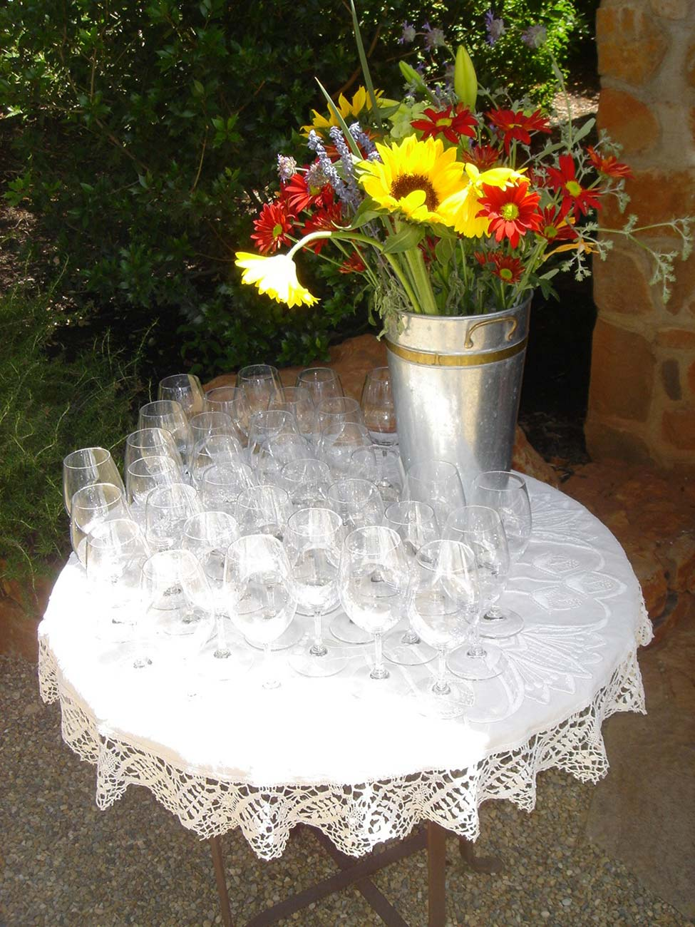 Small round table with wine glasses and a large metal vase filled with wild flowers