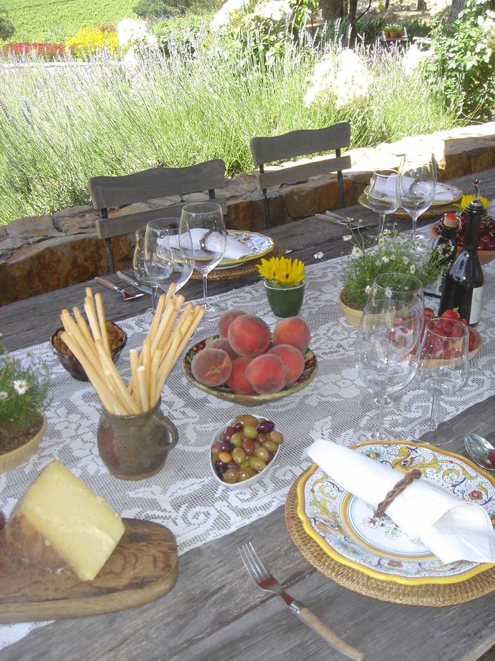 Tabletop design with bowls of peaches, olives, wild flowers and crystal