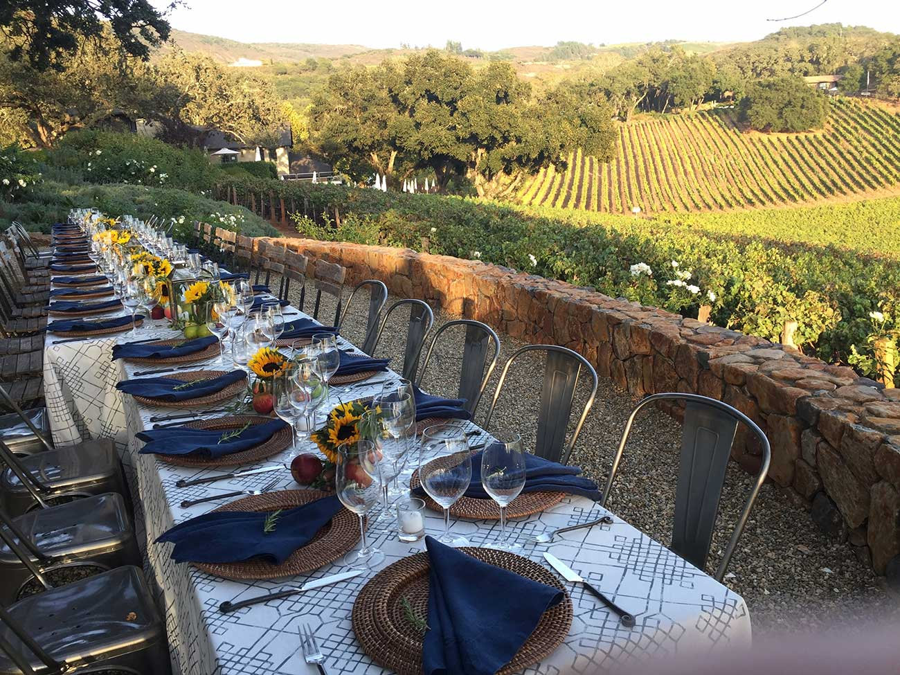 Tabletop design with crystal, dinnerware and sunflowers overlooking a vineyard