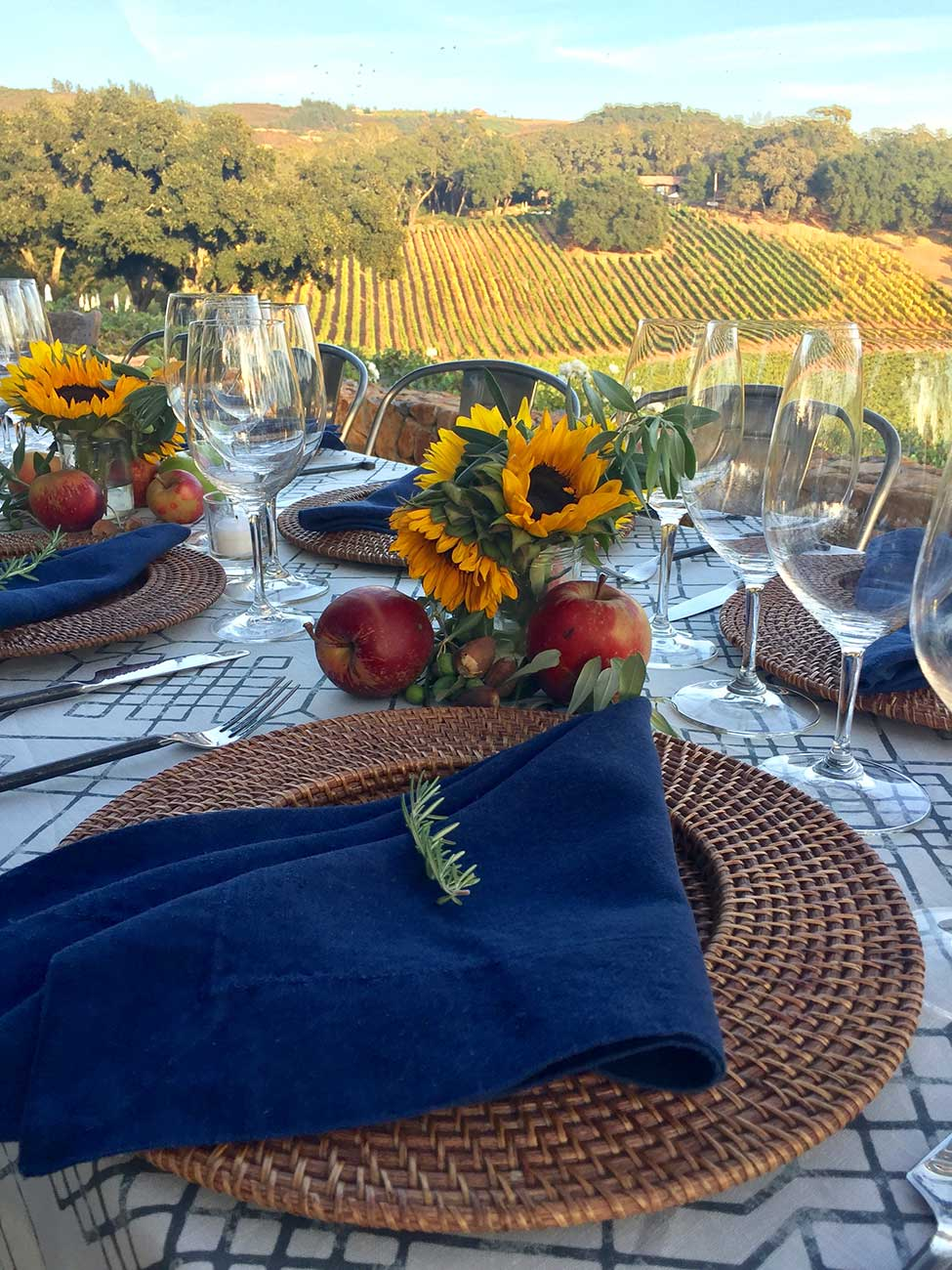 Tabletop design with crystal, dinnerware and sunflowers and apples overlooking a vineyard