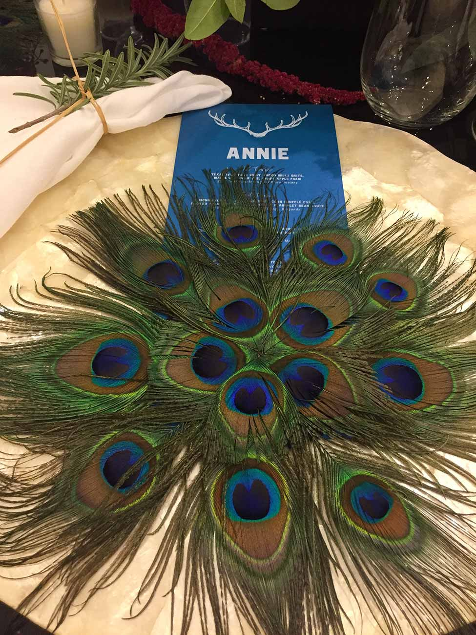 Closeup of Naples Wine Festival donation dinner tabletop design of peacock feathers in a circle over a plate and menu card