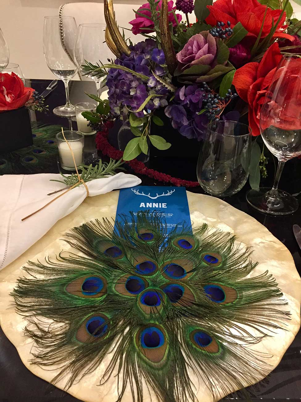Naples Wine Festival donation dinner tabletop design of peacock feathers in a circle over a plate and menu card