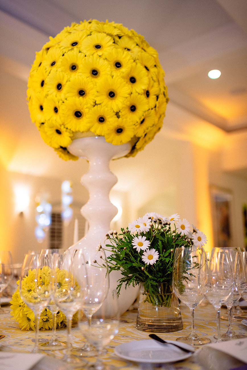 Yellow daisies in a white vase tabletop design for Naples Wine Festival Hamel