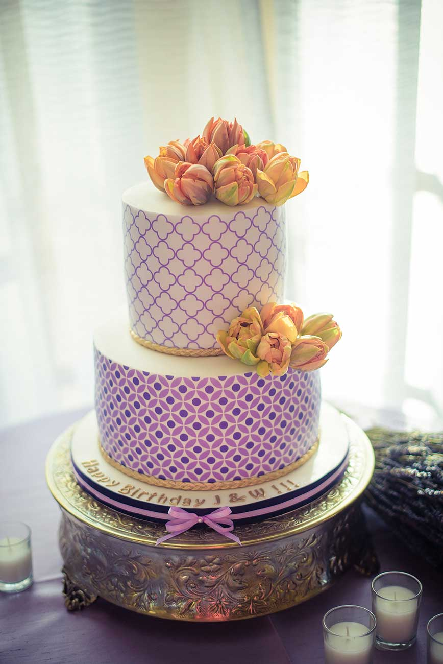 2 tiered royal purple and gold gingham cake with flowers