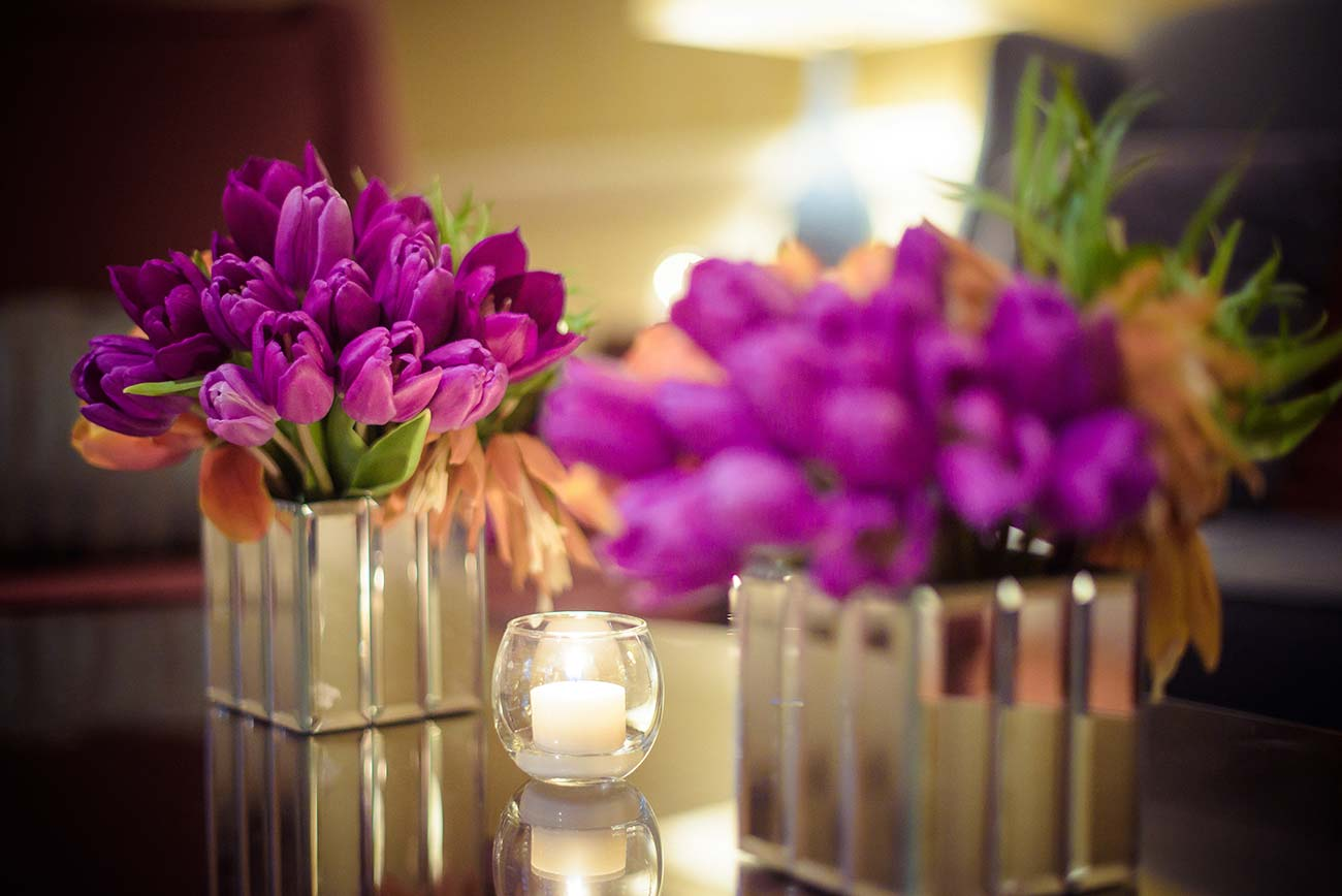 Two small glass vases with purple flowers and tea lights