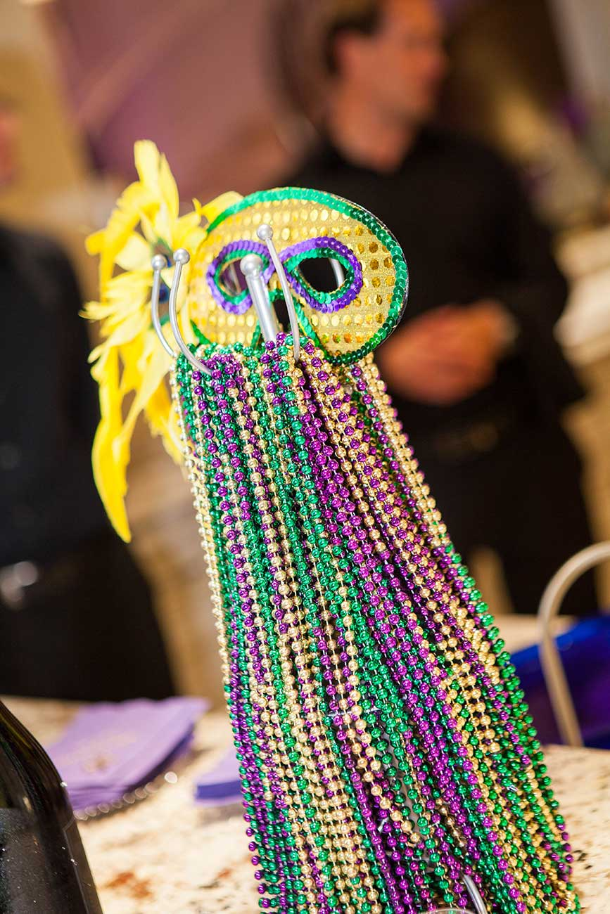 Colorful traditional Mardi Gras mask with beads hanging off the bottom of mask