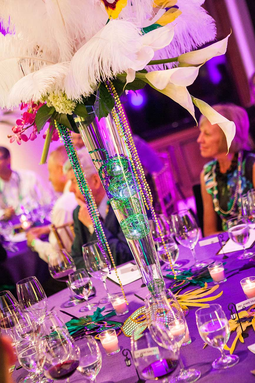 Tabletop design in Mardi Gras colors showing flowers, dinnerware and people smiling