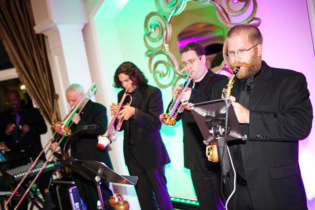 Band members playing different wind instruments on stage