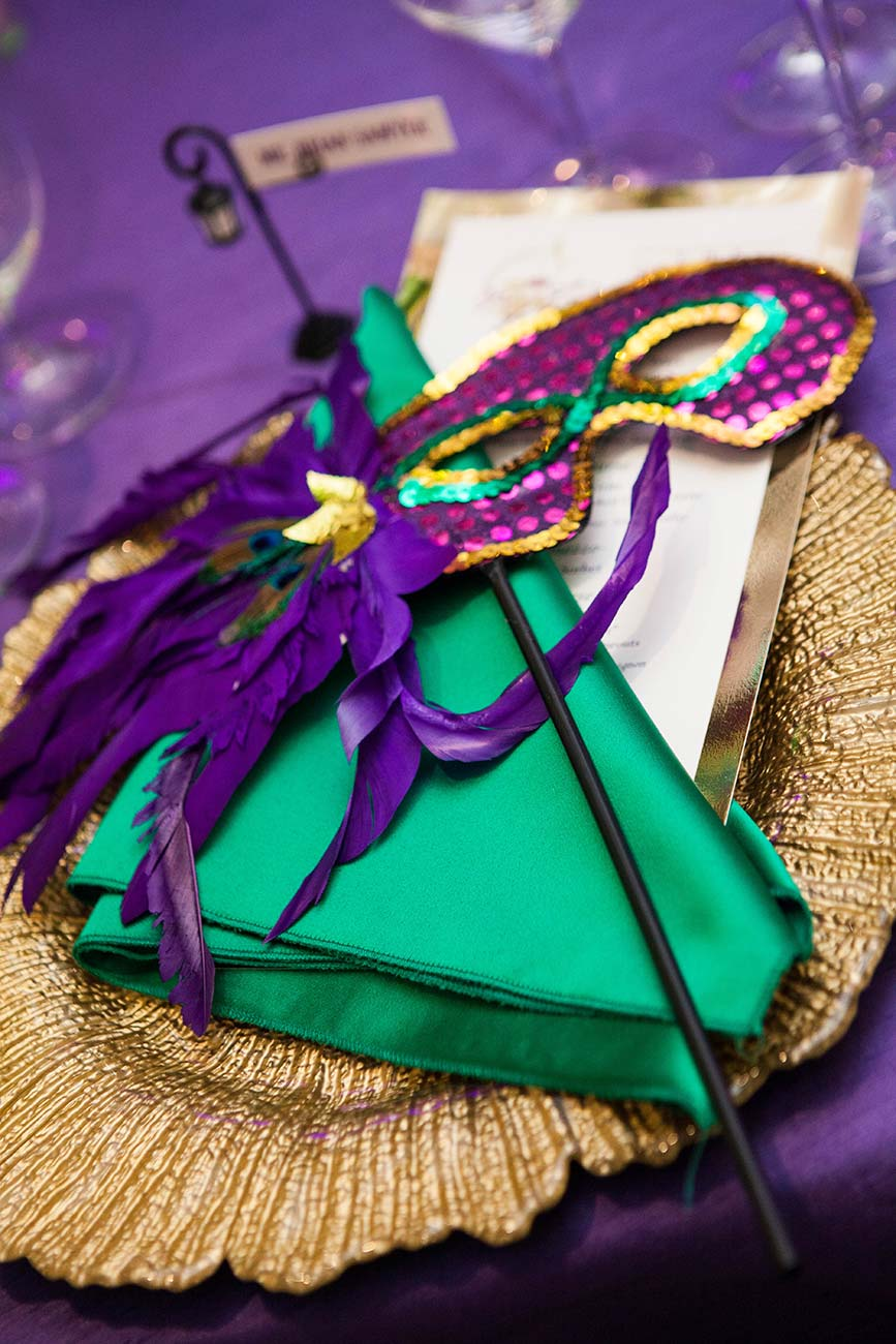 Mardi Gras inspired napkin and mask on top of gold charger and program event