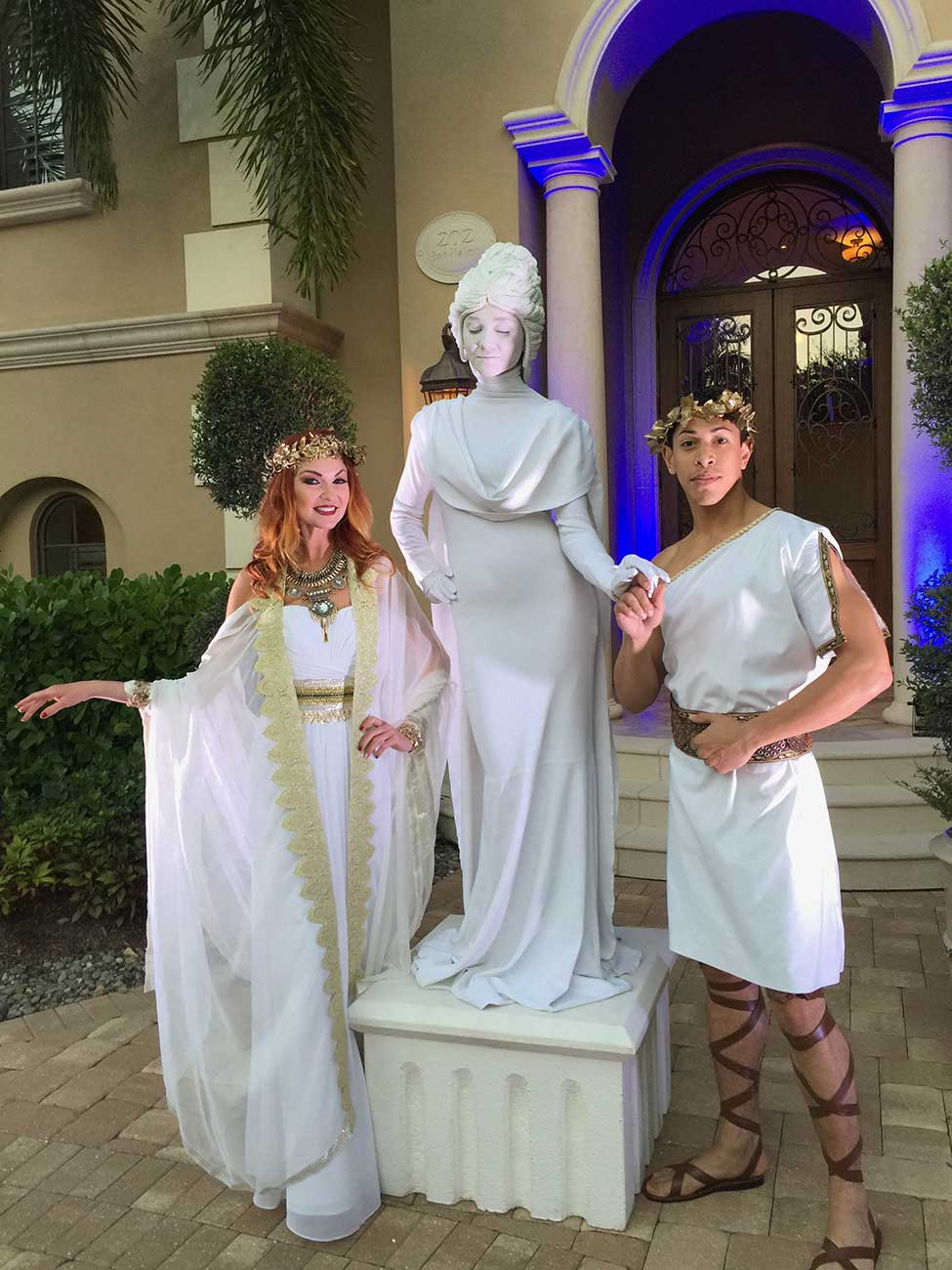 Greek statue and 2 actors dressed as Greek gods in front of home
