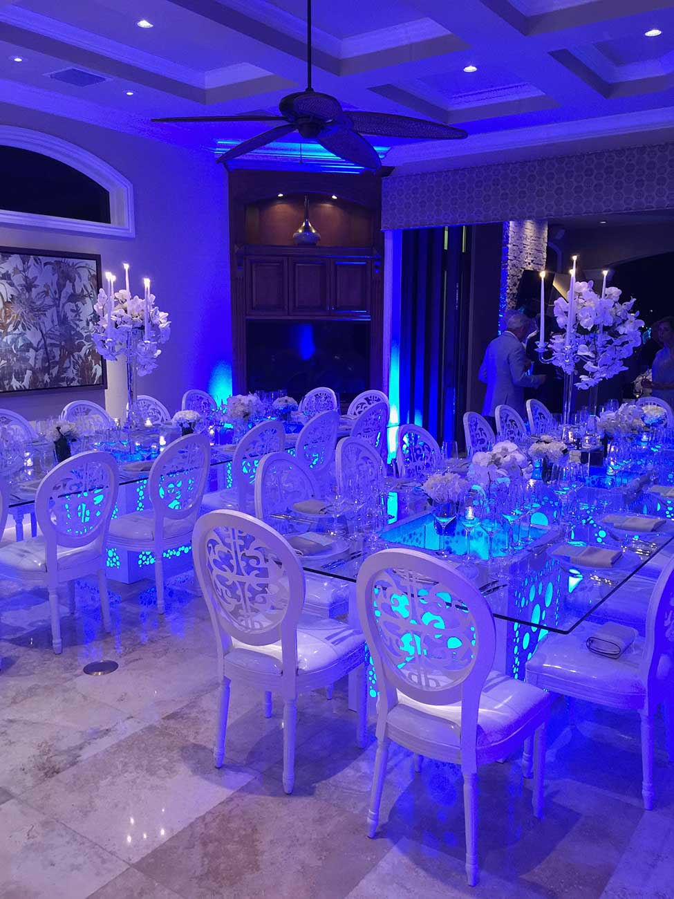 Tabletop design for 2 long glass tables inside with blue uplighting set in a modern tone