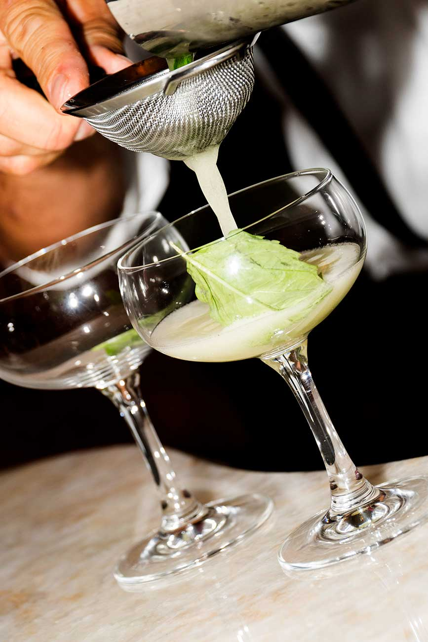 Cocktail being strained and poured into a glass
