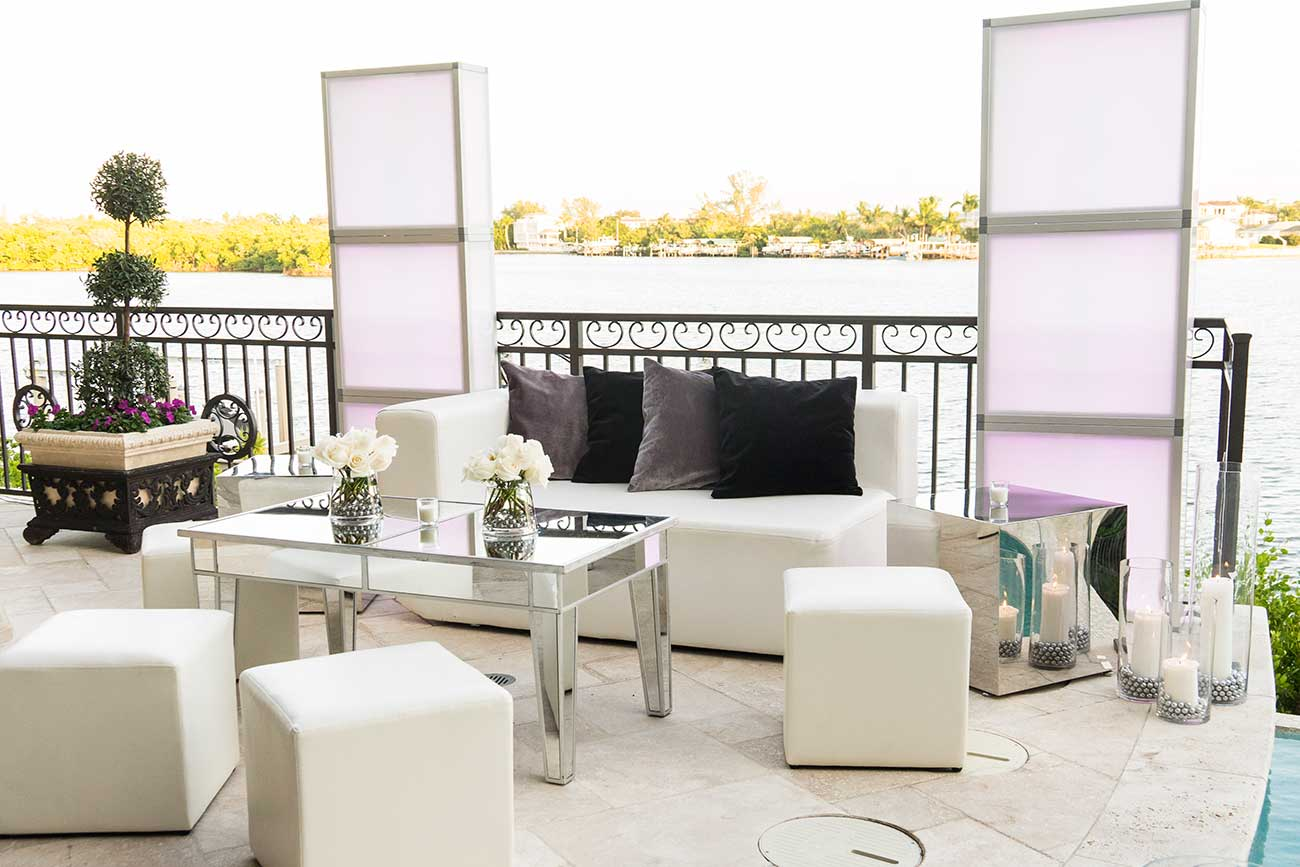 Porch set up with flowers and vases overlooking a bay