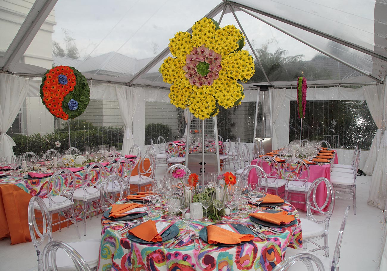 Tented tablescape in a 60's theme with bright colors and tall floral decor on each table