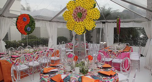 Tabletop design using a 60's inspired design with giant bright flowers, bright colors in an indoor tent