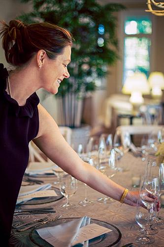 Margaret, founder of Margaret Events, adjusting stemware on a well-designed table top