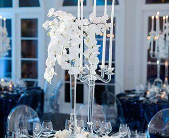 Tabletop design using white orchids, crystal vases, elegant dinnerware, stemware and blue uplighting