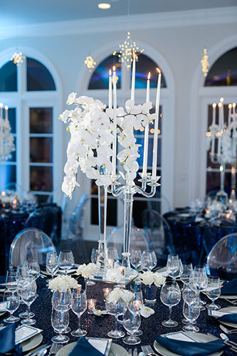 Tabletop design using white orchids, crystal vases, elegant dinnerware, stemware and blue uplighting