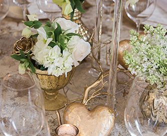 Table top design featuring stemware, silverware, white florals with a gold tone highlight
