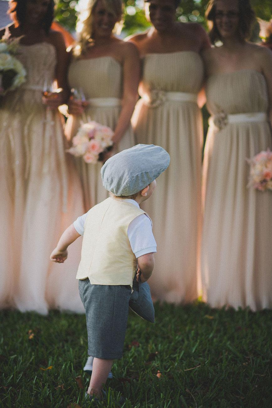 Little boy running towards bridesmaids
