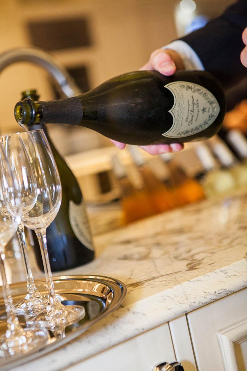 Server pouring Dom Perignon into champagne flutes