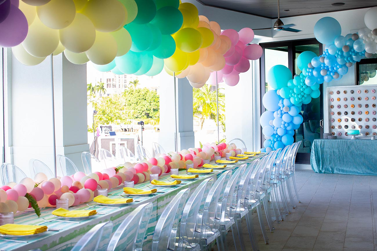 Tabletop design with ghost chairs, balloon canopy in rainbow colors designed for a Sweet 16 birthday party
