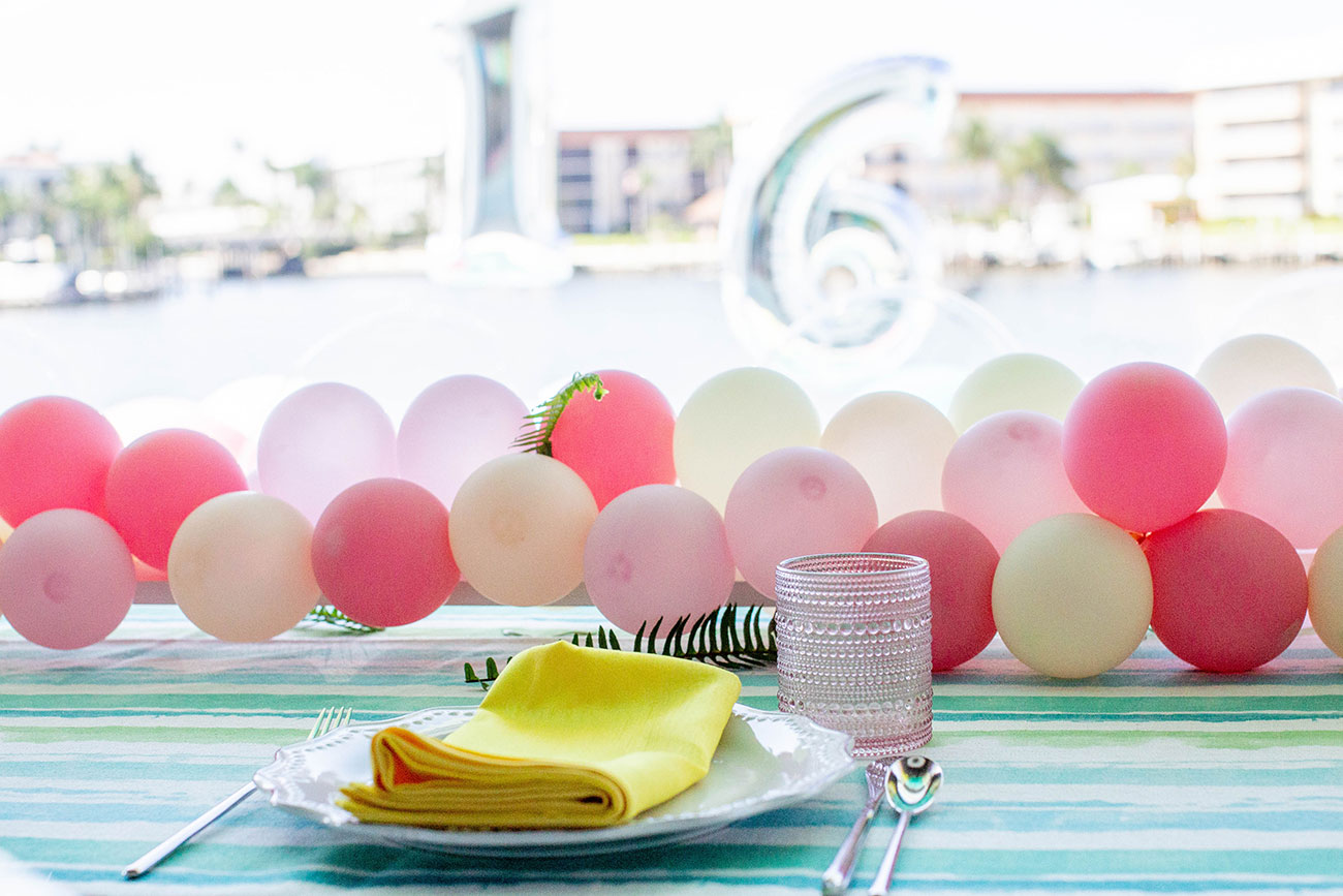 Yellow napkin and plateware with a pink and white balloon runner across table for a Sweet 16 birthday party