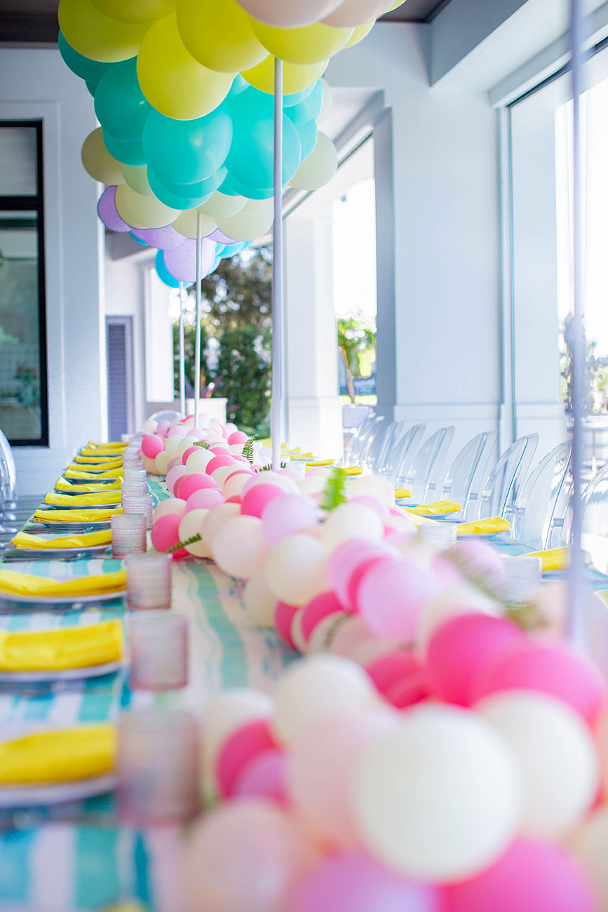 Yellow napkins and plateware with a pink and white balloon runner across table for a Sweet 16 birthday party