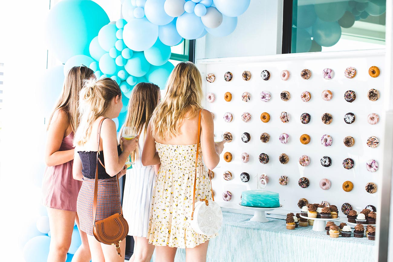 Three teenagers looking at a doughnut wall display