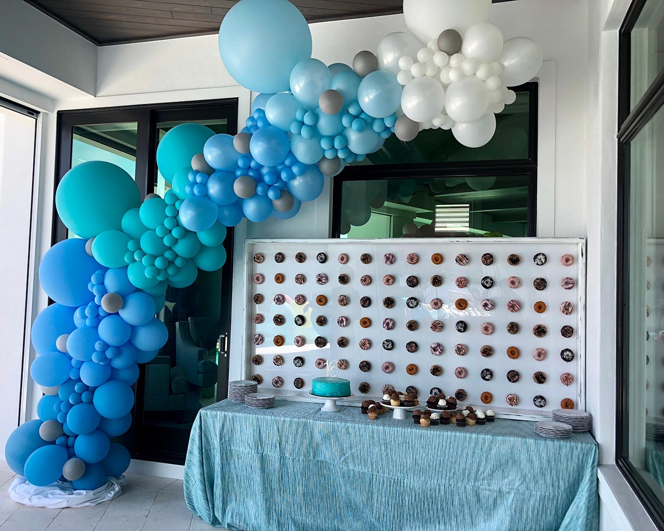 Blue balloon arch over dessert table at Sweet 16 birthday party