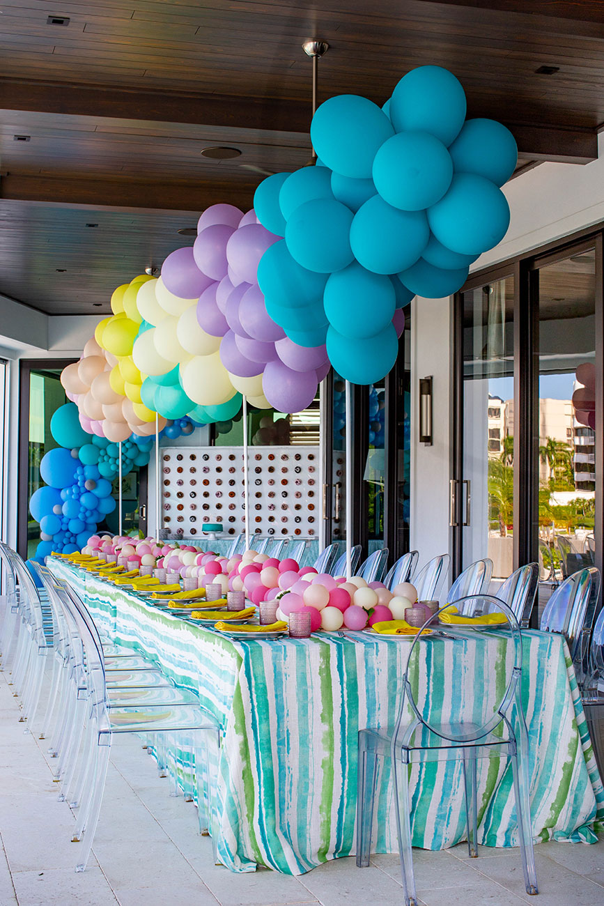 Rainbow arch of balloons set over a table that has been decorated with pink and white balloons for a Sweet 16 birthday party